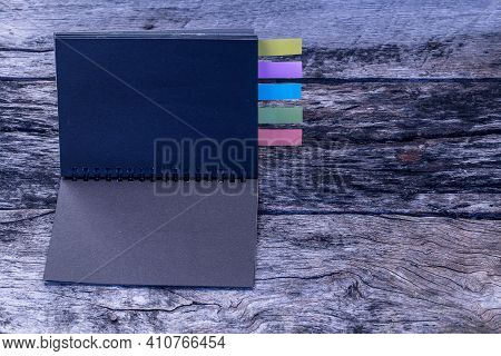 Black Diary With Colored Tabs. Five Colorful Bookmarks With Notebook , Closeup Of Colour Tabs For Bo