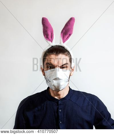 Young, Handsome Caucasian Man With Rabbit Ears And Protective Medical Mask Is Angry. Creative Banner