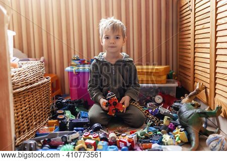 Cute Preschooler Boy Sitting On The Floor Among Plenty Of Toys, He Is Tired And Dull, Home Activity