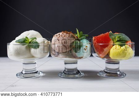 Set Of Ice Cream Scoops Of Different Colors And Flavors In Glass Sundae Bowls. Summer Delicious Food