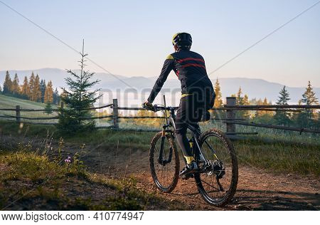 Back View Of Male Cyclist Riding Bike On Mountain Road With Coniferous Trees And Hills On Background