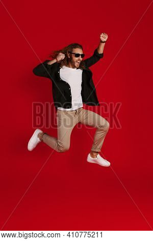 Full Length Of Cheerful Young Man In Casual Clothing Smiling And Gesturing While Hovering Against Re