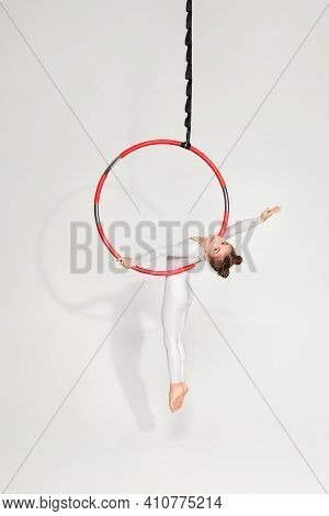 Cute Child Girl Gymnast In White Sportwear Shows An Acrobatic Performance On An Aerial Hoop. Acrobat