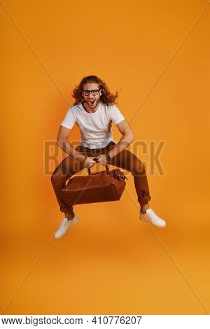 Full Length Of Playful Young Man Carrying Leather Bag And Making A Face While Hovering Against Yello
