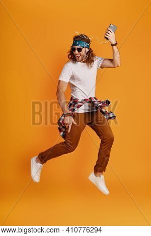 Full Length Of Happy Young Man Listening Music And Smiling While Hovering Against Yellow Background