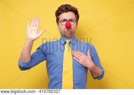 I Swear. Funny Young Manwith Red Clown Nose With Hand On Chest Giving Oath