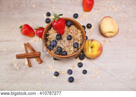 Photos Of Food. Oatmeal Porridge In Wooden Bowl. Still Life - Milk Porridge With Blueberries, Strawb