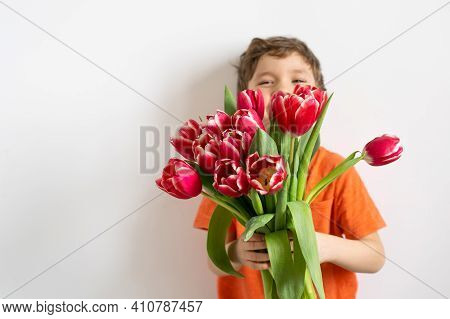 Cheerful Happy Child With Tulips Flower Bouquet. Smiling Little Boy On White Background.