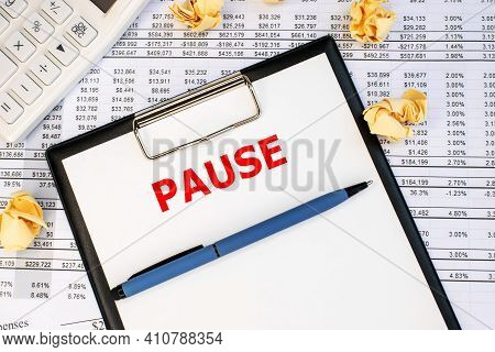 On The Financial Document Next To A White Calculator And Yellow Crumpled Sheets Of Paper There Is A