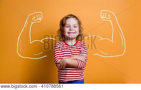 Strong Little Child With Muscles On Yellow Wall. Funny Kid With Crossed Hands. Confident Girl Ready