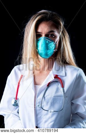 A young doctor poses with a N95 mask in a studio environment
