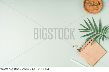 Flat Lay Of Green Working Place Table Background With Cup Of Coffee Putting On It. Flat Lay Notebook