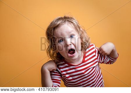 Little Girl Is Screaming. Portrait Of A Little Kid Shouting Isolated Over Orange Background. Angry P