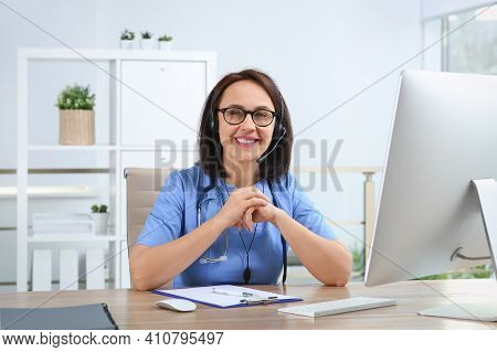 Doctor With Headset At Table In Office. Hotline Service