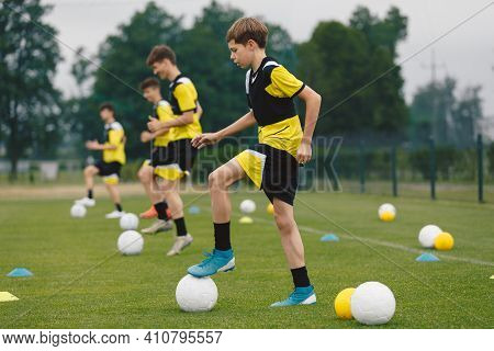 Teenage Boys Training Sports In A Row. Soccer Summer Camp For Young Boys. Happy Football Players On