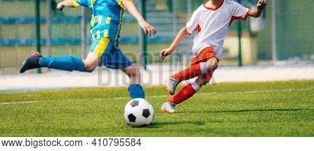 Two Soccer Boys Kicking Ball In Opposite Teams. Football Duel; Kicking Ball Moment. Young Football P