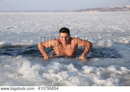Man Immersing In Icy Water On Winter Day. Baptism Ritual