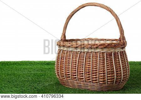 Empty Wicker Basket On Green Lawn Against White Background. Space For Design. Easter Item