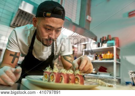 Portrait Of Experienced Sushi Chef Carefully Adding Final Touch With Dedication To His Delicious Sus
