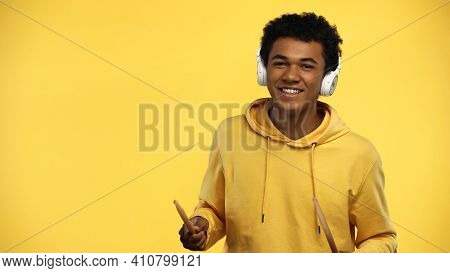 Happy African American Teenager In Wireless Headphones Holding Drumsticks Isolated On Yellow