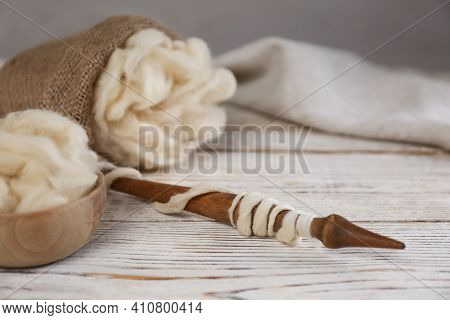 Soft White Wool And Spindle On Wooden Table. Space For Text