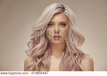 Gorgeous Woman With Beautiful Wavy Pink Hair On A Beige Background