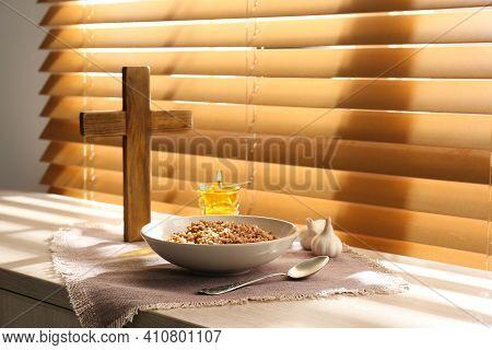 Buckwheat, Garlic, Wooden Cross And Candle On Window Sill Indoors. Great Lent Season