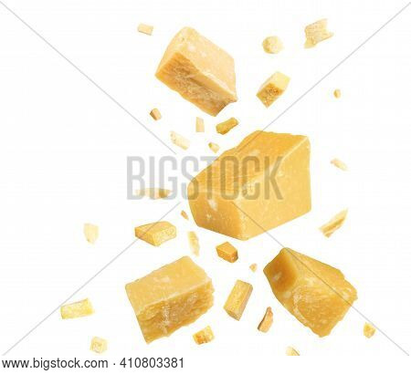 Pieces Of Delicious Parmesan Cheese Flying On White Background
