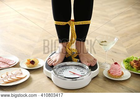 Food, Alcohol Left After Holidays And Woman With Measuring Tape Standing On Scales Indoors, Closeup.