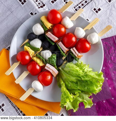 Antipasti on bamboo skewers with mozzarella, cherry tomatoes, ham; chees,  spinach and black olives on a white plate. Top view.