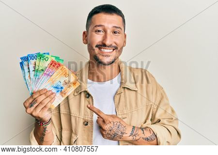 Handsome man with tattoos holding swiss franc banknotes smiling happy pointing with hand and finger