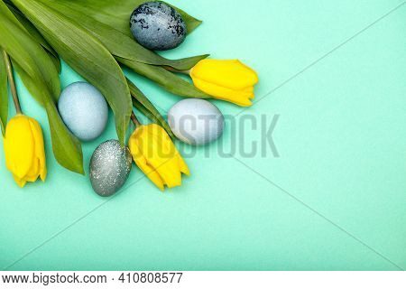 Easter Background, Bright Yellow Tulips With Easter Eggs Border Copy Space On Green Background.