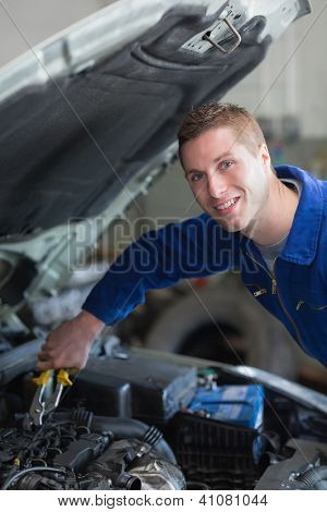 Portrait of happy male mechanic working on car engine