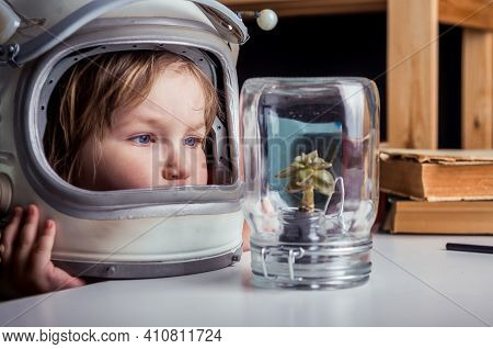 Little Girl In Space Suit Wearing Helmet And Discover Plant In Jar. Education For Kindergarten And S