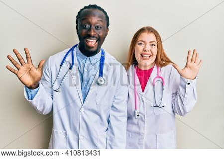Young interracial couple wearing doctor uniform and stethoscope showing and pointing up with fingers number ten while smiling confident and happy.