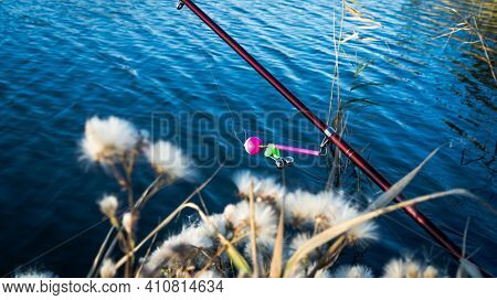 Fishing Rod With A Bell On The Lake In The Autumn. Toned Photo With The Vignetting.