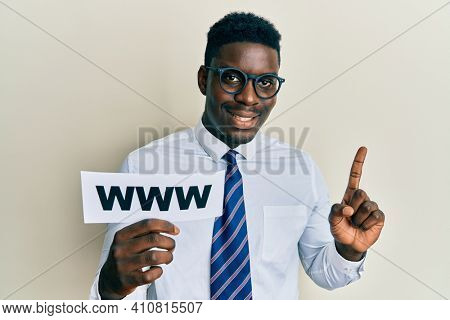 Handsome black man holding www on paper smiling with an idea or question pointing finger with happy face, number one