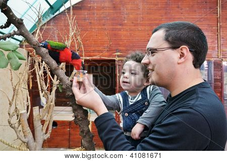 Portrait Of Happy Father And His Daughter Feeding Parrot