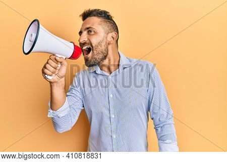 Handsome man with beard shouting through megaphone angry and mad screaming frustrated and furious, shouting with anger. rage and aggressive concept.