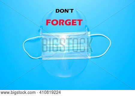 A Picture Of Face Shield And Mask With Don't Forget Wordon Blue Background. Face Shield Is Needed An