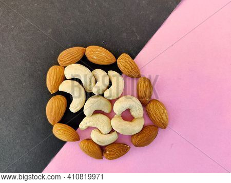 Pieces Of Cashew Nuts Surrounded By Almonds Isolated On Pink And Black Background