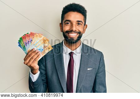 Handsome hispanic business man with beard holding swiss franc banknotes looking positive and happy standing and smiling with a confident smile showing teeth