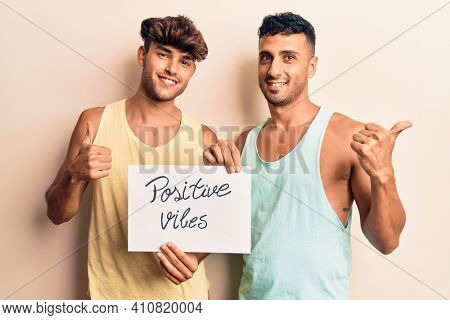 Young gay couple holding positive vibes banner smiling happy and positive, thumb up doing excellent and approval sign