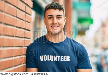 Young hispanic volunteer man smiling happy standing at the city.