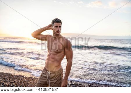 Handsome Young Muscular Italian Man Posing Shirtless On The Beach, Sunset Summer Time. Ideal Fit Bod