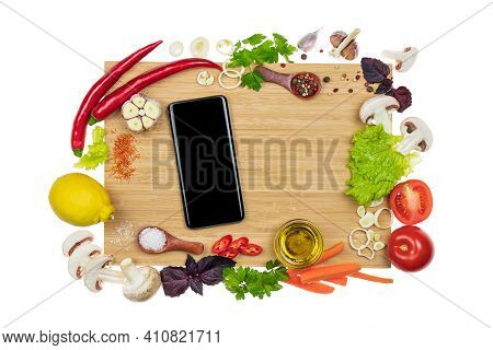 Ingredients, Herbs And Spices Around Smartphone Mock Up With Empty Screen On Cutting Board. Concept