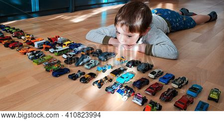 Kirchheimbolanden Germany- November 15 2020: 5-year-old white Caucasian boy lies on floor,boredom on face in front of plenty toy cars.Overconsumption concept,home quarantine is boring.Selective focus.