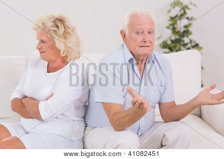 Woman being angry against a missunderstanding man on the sofa