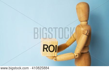 Wooden Man Holding A Wooden Cube With Acronym Roi. Business And Finances Concept.