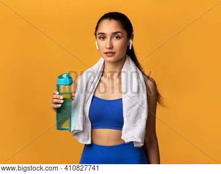 Stay Hydrated. Portrait Of Confident Sporty Young Lady With White Towel On Neck Holding Bottle With